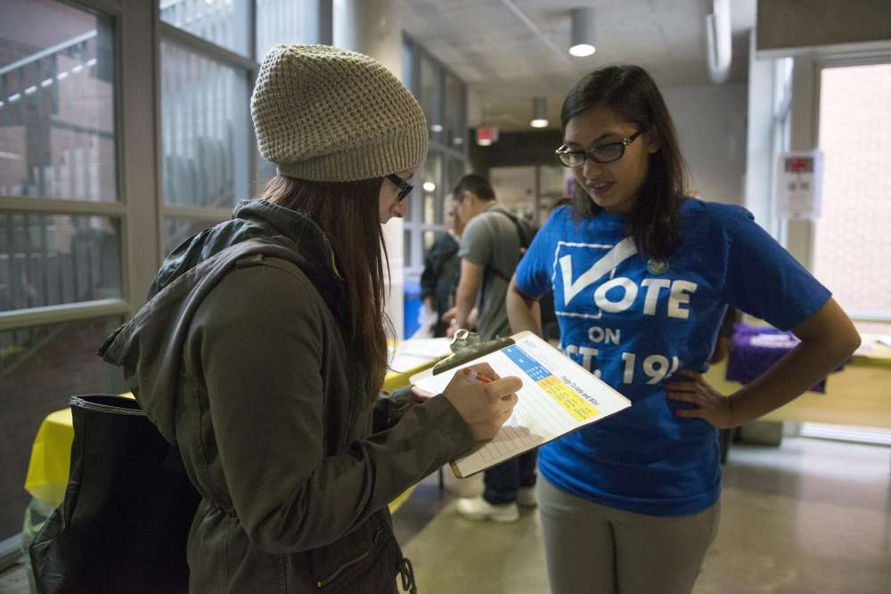 Rabbia Ashraf, vice-president internal at the Continuing Education Students' Association of Ryerson (CESAR) talks to 2nd year student Katey Agnitsch about voting. Elections Canada set up advance polling stations on the second floor of the Ryerson Student Centre at Ryerson University in Toronto, Wednesday, Oct, 7, 2015. THE CANADIAN PRESS/Marta Iwanek